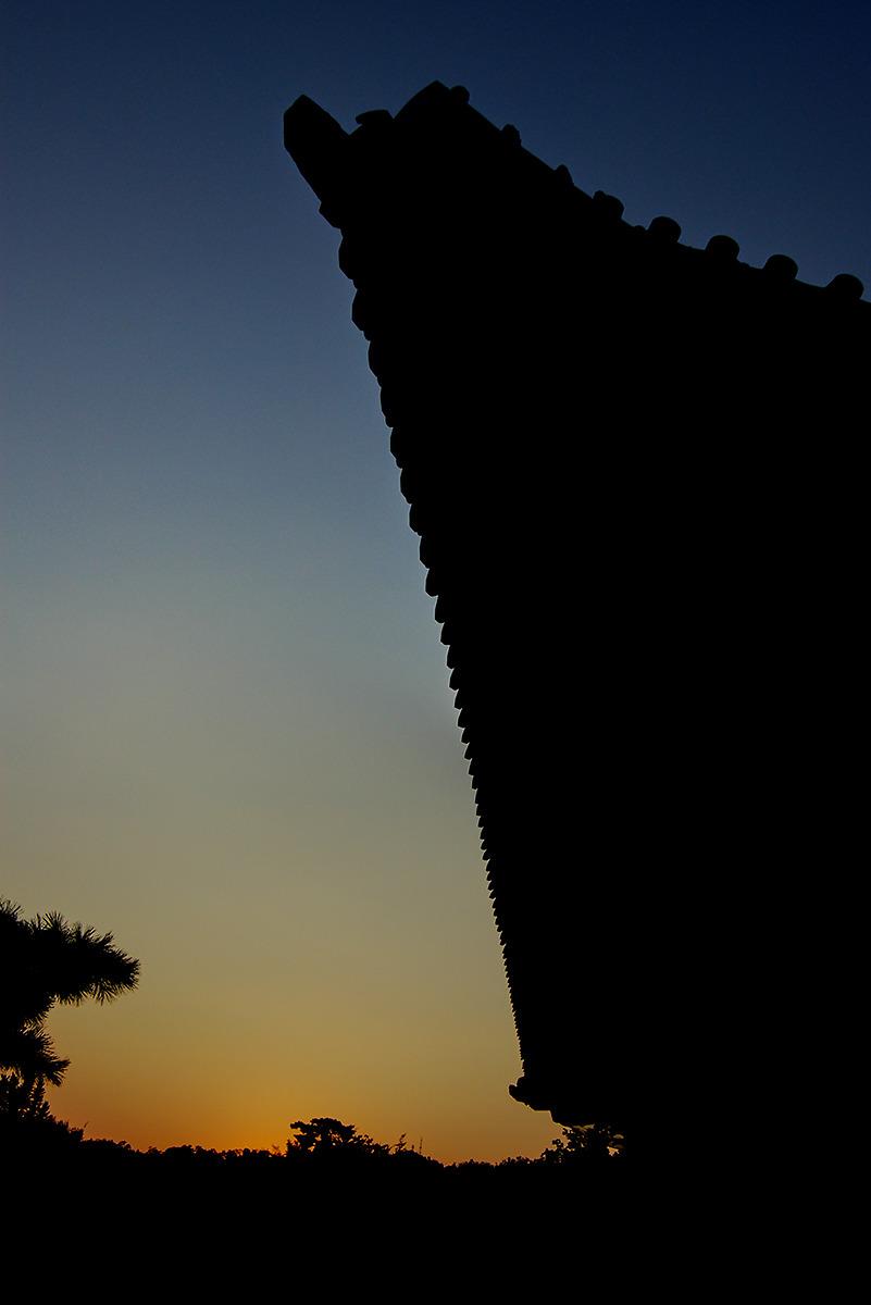노을이 떨어지는 하늘은 붉으스름하게 보이며 역광으로 촬영되어 처마의 모양이 실루엣으로 표현되어있다.