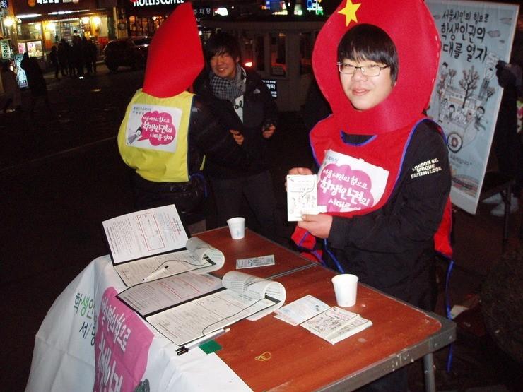 청소년활동가들이 머리에 촛불 모양 장식을 쓰고 거리에서 서명을 받고 있는 모습이다. '서울시민의 힘으로 학생인권의 시대를 열자'는 문구가 활동가들이 입은 조끼와 뒤편으로 보이는 피켓, 가판대에 걸린 현수막에 쓰여있다.