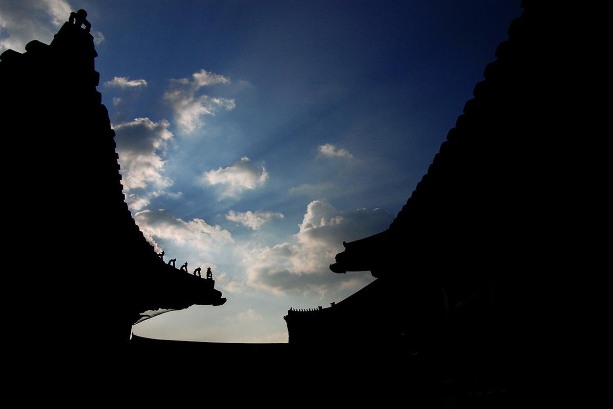 (경복궁사진) 역광으로 촬영된 여러채 건물의 실루엣만 보이고 그 뒤로 파란 하늘과 구름이 보인다. 삼장법사와 졸개를 뜻하는 어처구니구(잡상)이 도드라지게 표현되어있다.